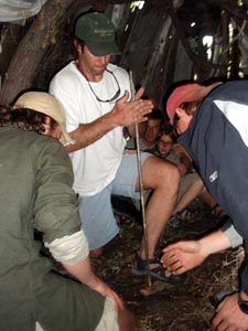 Starting a handdrill fire inside a wickiup on a survival skills adventure.